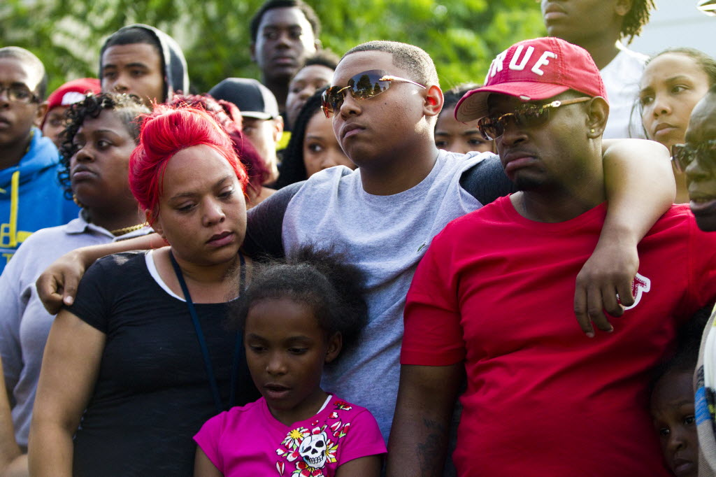 Arifah Akbar, Nazir Akbar and Katraile Scott stand together during a vigil for Tariq Akbar, on July 7. Tariq was shot to death July 3 in Milwaukee, after watching a fireworks display with his friends. Photo by Katie Klann of the Milwaukee Journal Sentinel.