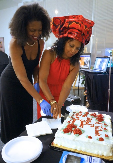 Dawn Sanders (left), daughter of the late Welford Sanders, and Marquita Edwards, artistic director of the King Drive Commons Gallery and Studio, cut a piece of cake during a celebration of the late developer's contributions to the community. Photo by Adam Carr.