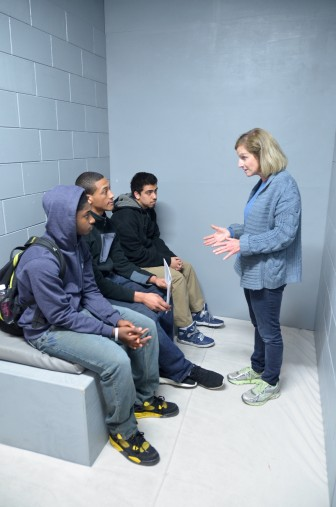 The statewide faith-based group, Wisdom, commissioned construction of this mock-up of an isolation cell for its campaign against solitary confinement. Here, Wisdom volunteer Jane Miller talks with students visiting the cell at Marquette University in March. Photo by Lauren Fuhrmann of the Wisconsin Center for Investigative Journalism.