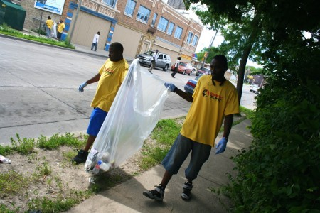Khalil Coleman and Teddy Ellis (right) pick up garbage on W. Atkinson Avenue in Garden Homes, setting an example for young people in the neighborhood. Photo by Jabril Faraj.