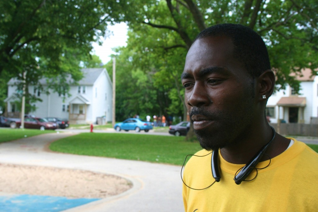Teddy Ellis stands in Garden Homes Park while a group of neighborhood youth gamble across the street. Photo by Jabril Faraj.