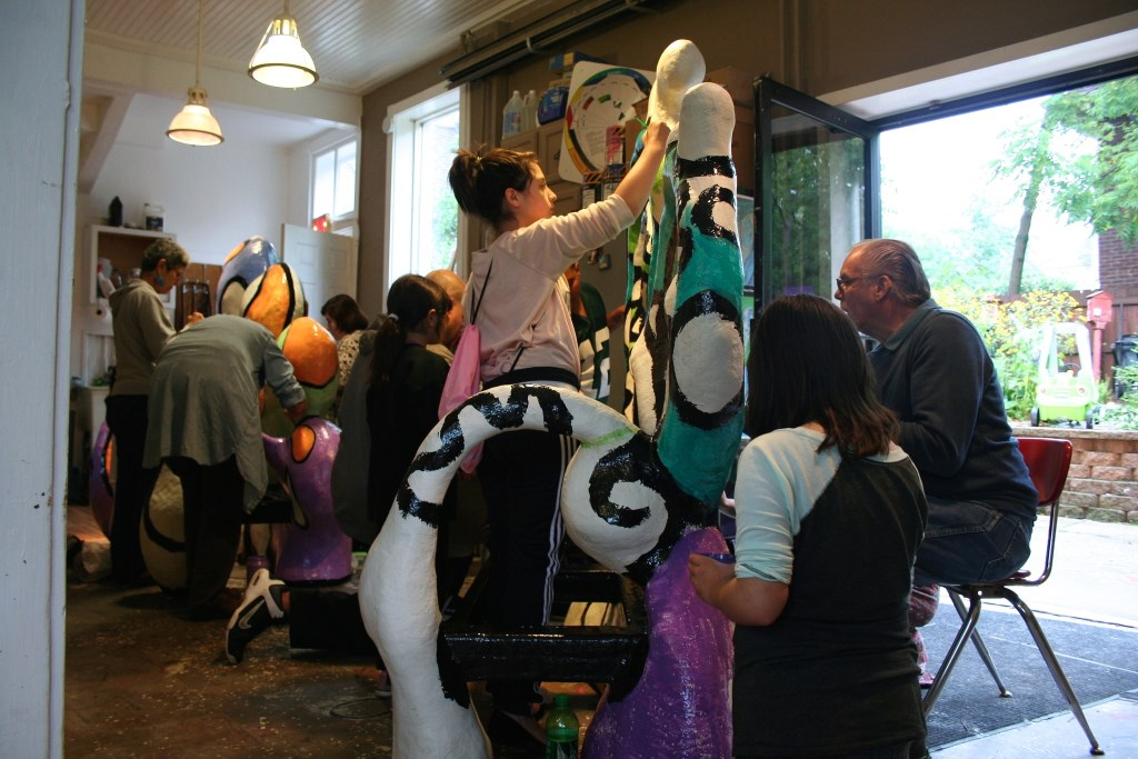 """Volunteers paint a sculpture named """"Water Heart"""" that will be installed in Pulaski Park. Photo by Jabril Faraj."""