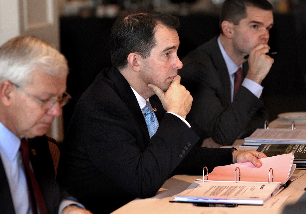 Gov. Scott Walker, then-chairman of the Wisconsin Economic Development Corp., participates in a WEDC board meeting in late 2013 in La Crosse along with CEO Reed Hall, left, and then-chief operating officer Ryan Murray. Walker removed himself in July as chairman of the board after a negative audit and critical news coverage of the job-creation agency. Murray has left the agency, and Hall will retire in September. Hall's replacement is longtime banker Mark Hogan. Photo by Peter Thomson of the La Crosse Tribune.
