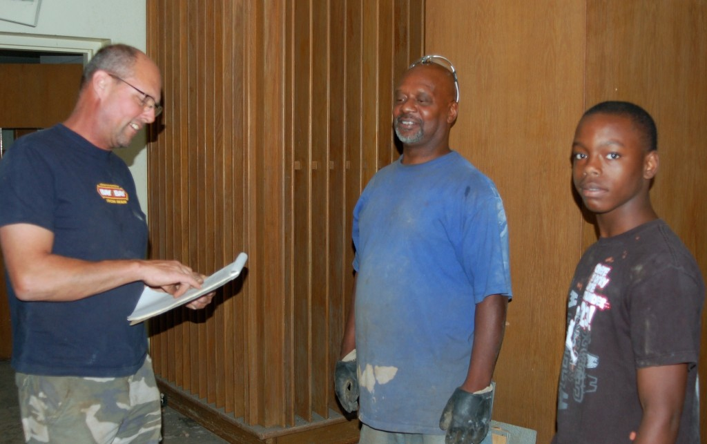 Matt Bohlmann (left), the new owner of the former Finney Library building, consults with Ken Maclin (center) and Dontrell Jackson about demolition work they are doing at the site. Photo by Andrea Waxman.