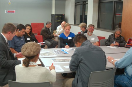 Representatives from the Department of City Development discuss preliminary recommendations for Walker Square with local residents. Photo by Edgar Mendez.