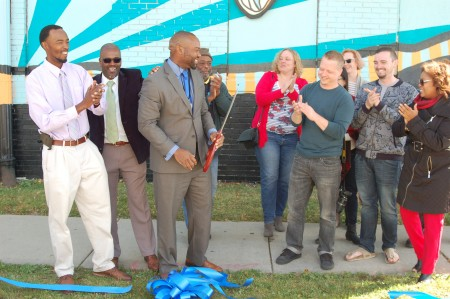 Alderman Russell W. Stamper II cuts a ribbon as community leaders and Washington Park residents celebrate a new mural marking the neighborhood's entrance. Photo by Andrea Waxman.