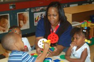 Nikole Foster, an early childhood education teacher, helps students with an art project at the Northside YMCA location. Photo by Stephanie Harte.