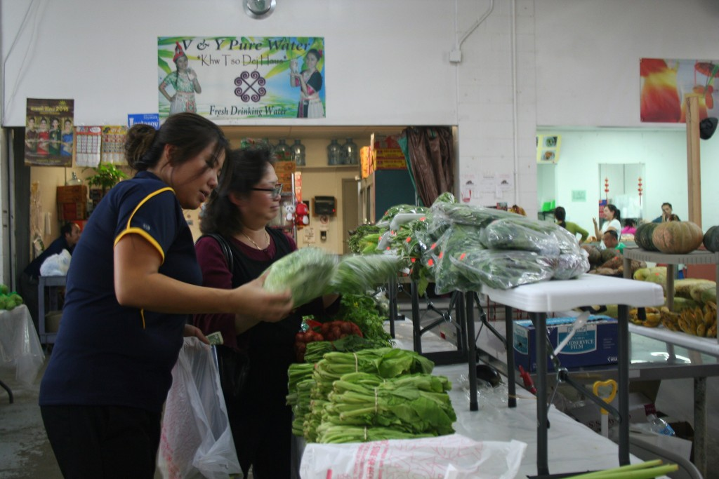 Mailee Yang, who is the daughter of the Phongsavan Market's owner Pai Yang, helps a customer pick out fresh vegetables. Photo by Jabril Faraj.