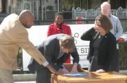 Kieth Stanley, Chris Abele, and Rana Altenburg sign the development fund. Photo by Michael Holloway.