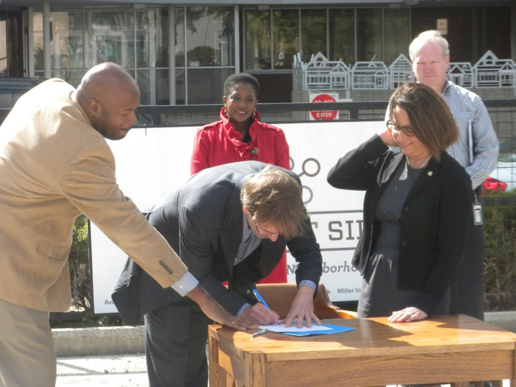 Kieth Stanley, Chris Abele, and Rana Altenburg sign the development fund. Photo by Michael Holloway.