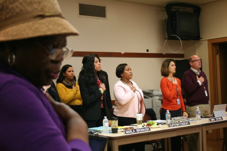 Director Annie Woodward (left foreground) and MPS administrators recite the pledge of allegiance before a retreat focused on charter schools. Photo by Jabril Faraj.