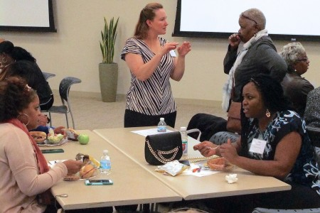 Adrian Spencer (seated, right), Safe & Sound District 5 community organizer; Paula Butler (standing, left); and Jeanette Mitchell (standing, right) discuss community safety at the symposium. Photo by Wyatt Massey.