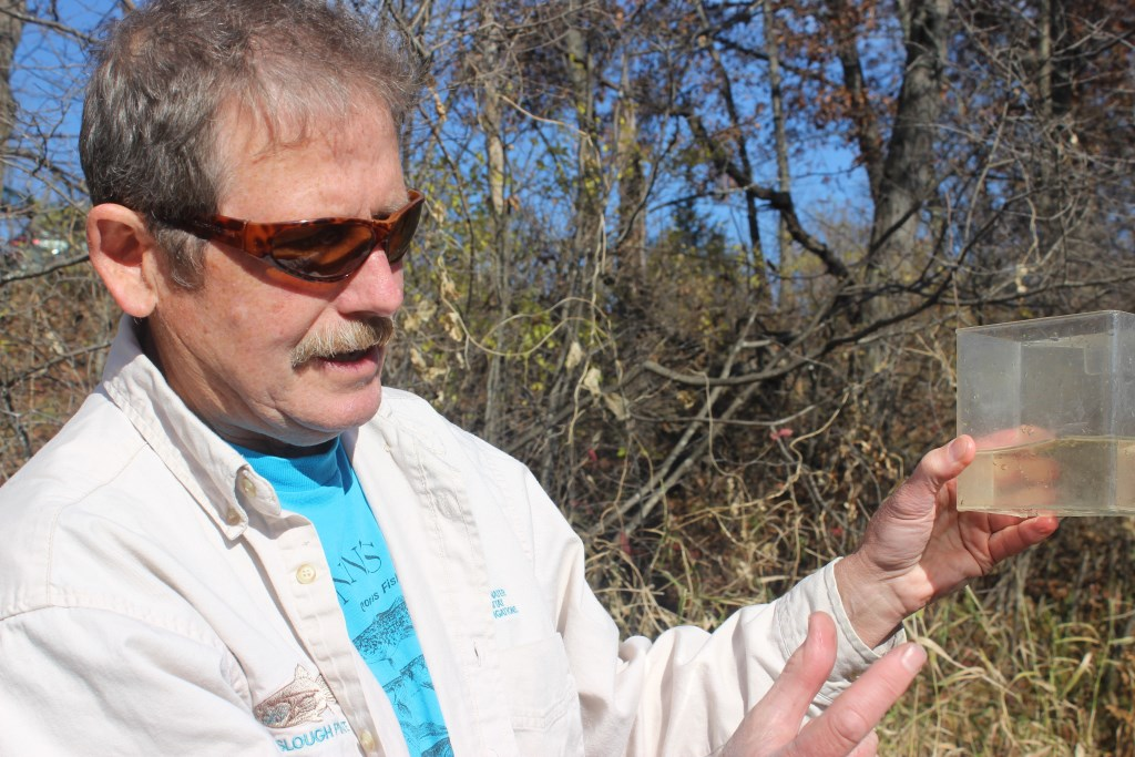 Dave Marshall, a former Department of Natural Resources scientist from Barneveld, holds upa sample from the Wisconsin River, which he said is polluted by nitrate. Some of his neighbors' wells also are contaminated with unsafe levels of nitrate. Marshall is one of 16 Wisconsin residents who have filed a petition with the U.S. Environmental Protection Agency asking for the state DNR's authority to administer part of the Clean Water Act to be revoked if it does not correct deficiencies. Photo by Bridgit Bowden of the Wisconsin Center for Investigative Journalism.