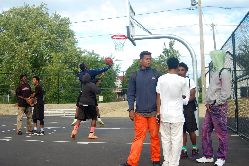 Young men wait their turn to play basketball during the opening day celebration at Moody Park. Photo by Edgar Mendez.