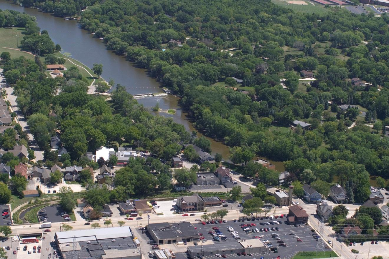 Aerial photograph (from 2012) showing the Mequon-Thiensville Dam (center left) and the residential neighborhood to the south (upper portion of photo) that includes homes that are both upstream of the Dam (with access to the 700-acre impoundment and uses that include recreational boating), and homes that are downstream of the dam with no access to the impoundment.