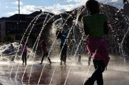 Neighborhood youth play in the splash pad after opening ceremonies for the renovated Moody Park. Photo by Adam Carr.