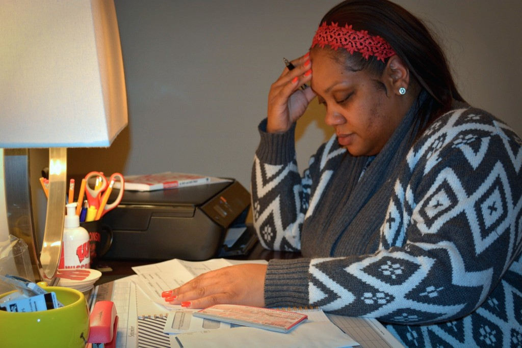 Latoya S. sits at her desk looking through overdue bills. Since 1998, she's taken out close to 20 short-term payday loans. Photo by Marlita A. Bevenue.