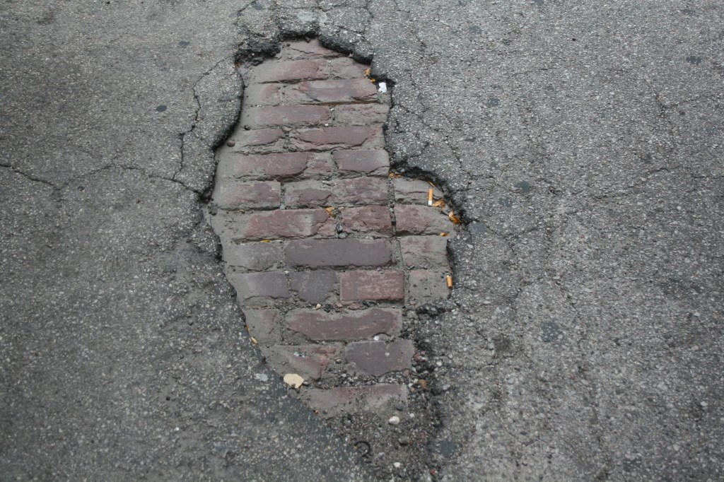 Brick pavers are exposed as the asphalt has crumbled away. Photo by Jeramey Jannene.