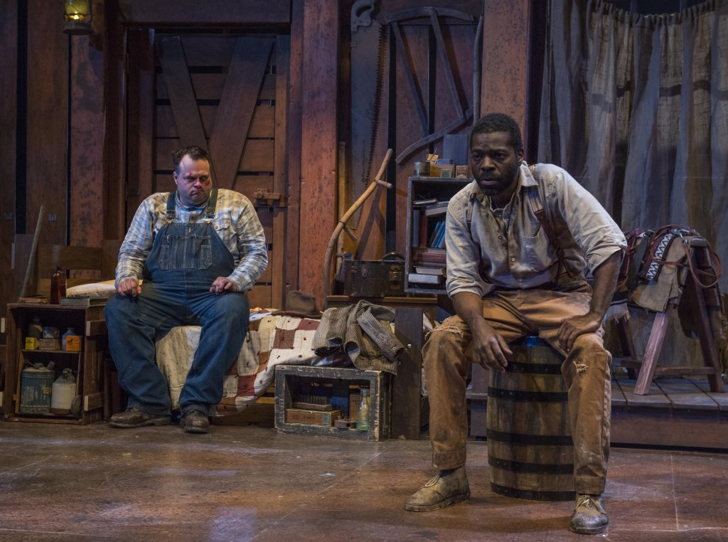 Milwaukee Repertory Theater presents Of Mice and Men in the Quadracci Powerhouse from January 19 to February 21, 2016. Left to right: Scott Greer and Chiké Johnson. Photo by Michael Brosilow.