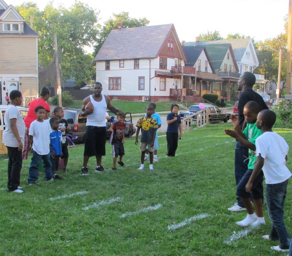 Field manager Markevin Brown holds the football at the 2012 opening of Fox Field, a vacant lot transformed by Safe & Sound and residents of the 2000 block of North 41st Street. Photo by Andrea Waxman.