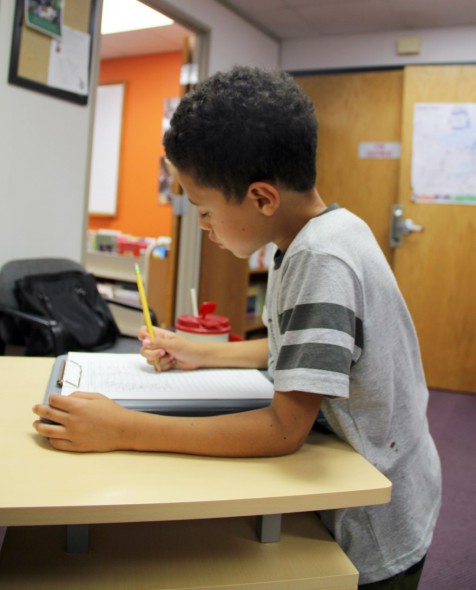 Third-grader Damare McCollum signs in to use a computer after school at the Packer Townhouses community learning center in Madison. Photo by Abigail Becker of the Wisconsin Center for Investigative Journalism.