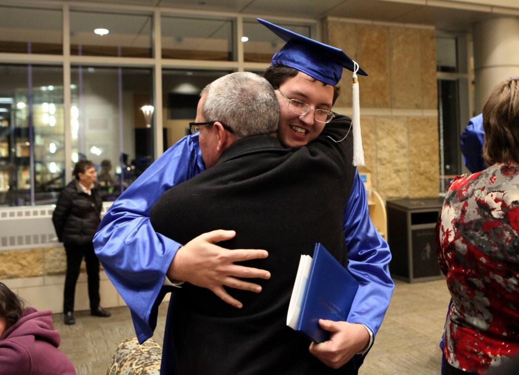 Ien Roder-Guzman, 24, hugs his dad Scott Roder after Madison College's graduation ceremony in December. Photo by Coburn Dukehart of the Wisconsin Center for Investigative Journalism.
