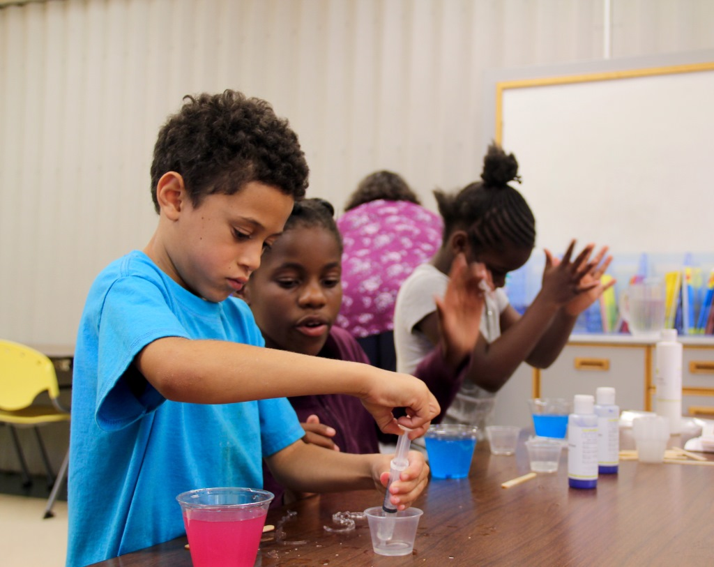 T'Asia Mondie, grade 5, looks over third-grader Damare McCollum's project during a weekly Science Club meeting at the Packer Townhouses community learning center in Madison. Photo by Abigail Becker of the Wisconsin Center for Investigative Journalism.