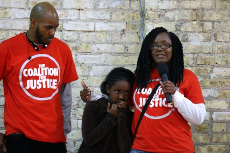Markasa Chambers (left) and Nate Hamilton, co-founder of the Coalition for Justice, comfort Zoe Chambers, 8, as she tries to speak to the group. Photo by Jimmy Gutierrez.