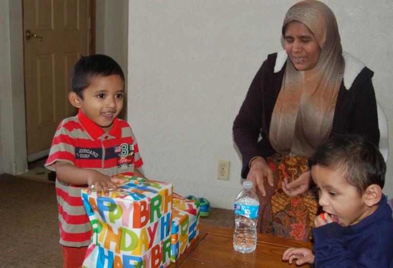 Sufaidul Sirajul Kadir, 3, opens a birthday present from International Institute volunteer Cindy Angelos as his grandmother, Saliya Begum binti Jalal Ahmad, and younger brother, Hubaib Sirajul Kadir, 2, look on. Photo by Andrea Waxman.