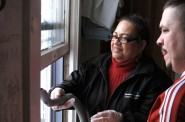 Carmen Reinmund (left) vacuums chipped lead paint from a windowsill as South Side homeowner Armando Martinez watches. Photo by Wyatt Massey.