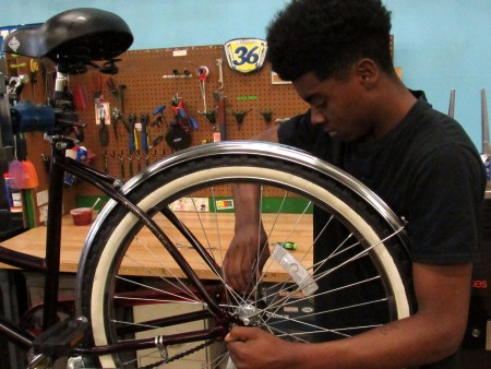 Devin Burton, 18, has been working at DreamBikes as a bicycle mechanic for the past two years. Photo by Morgan Hughes.