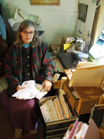 Prisoner rights advocate Peg Swan, in her home office, with letters from inmates at Waupun Correctional Institution. She says she has been hearing for about a year about high lead levels in the water at the 150-year-old prison. Photo by Linda Falkenstein.
