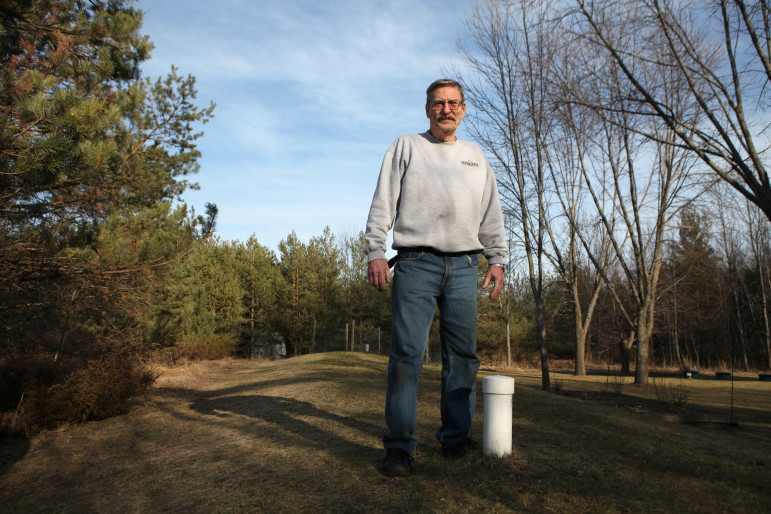 Alan Ashley stands on his mound septic system in Ephraim, Wisconsin, on March 12, 2016. In 1975, Ashley installed what he says was one of the first mound systems in Door County. The cost to replace the system for his four-bedroom house in 2007 was around $14,000. Photo by Coburn Dukehart of the Wisconsin Center for Investigative Journalism.