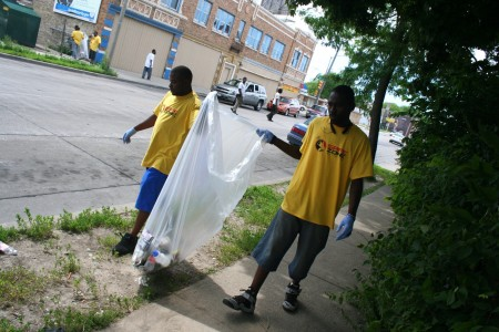 Safe Zones co-founder Khalil Coleman (left) and ambassador Teddy Ellis pick up garbage on W. Atkinson Avenue in Garden Homes. Photo by Jabril Faraj.