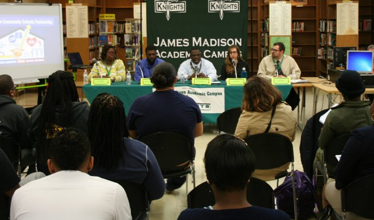 James Madison Principal Gregory Ogunbowale (center) speaks to community members and parents during a recent event focused on community schools. Photo by Jabril Faraj.