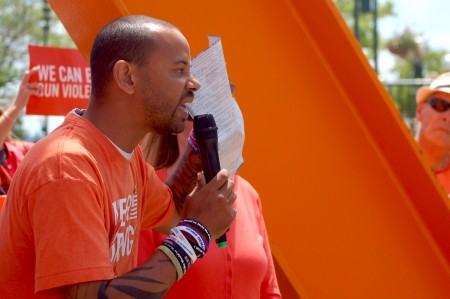 Khary Penebaker, a candidate for U.S. Congress, holds his mother's death certificate as he tells a crowd at a gun violence awareness rally about her suicide in 1979. Photo by Brendan O'Brien.