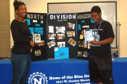 Tatiana Loyd and Qiaira Mathews pose with their app displayed on tablets. Photo by Rebecca Carballo.
