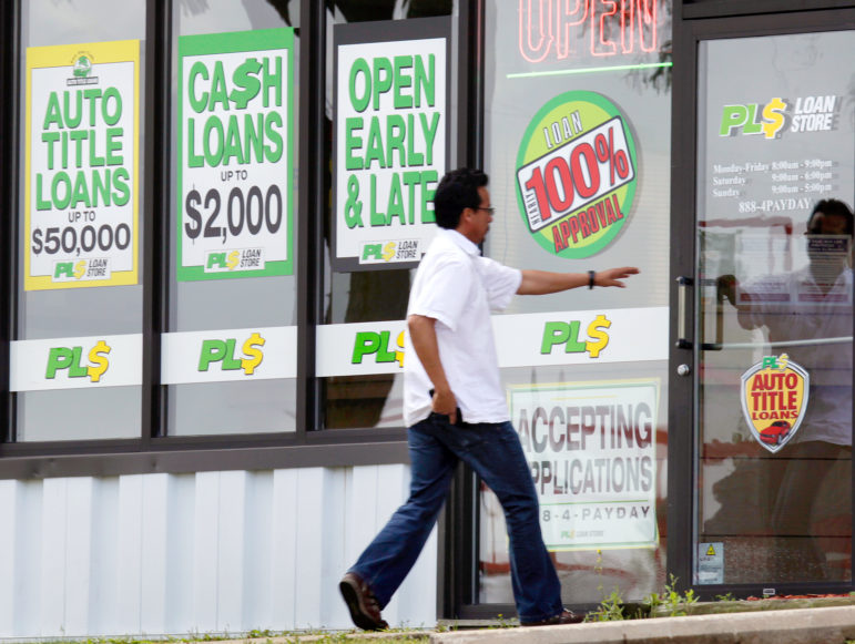 A customer enters the PL$ Payday Loan Store on Red Arrow Trail in Madison. In 2015, the average annual interest rate on payday loans in Wisconsin was 565 percent. Photo by Mike DeVries of The Cap Times.