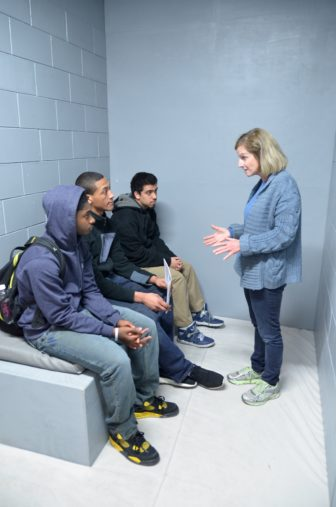 The statewide faith-based group, Wisdom, commissioned construction of this mock-up of an isolation cell for its campaign against solitary confinement. Here, Wisdom volunteer Jane Miller talks with students visiting the cell at Marquette University in March 2015. Wisdom is supporting the Wisconsin inmate hunger strike aimed at eliminating administrative confinement, a status in which prisoners are allowed to be held in solitary confinement for prison safety reasons indefinitely. Photo by Lauren Fuhrmann of the Wisconsin Center for Investigative Journalism.