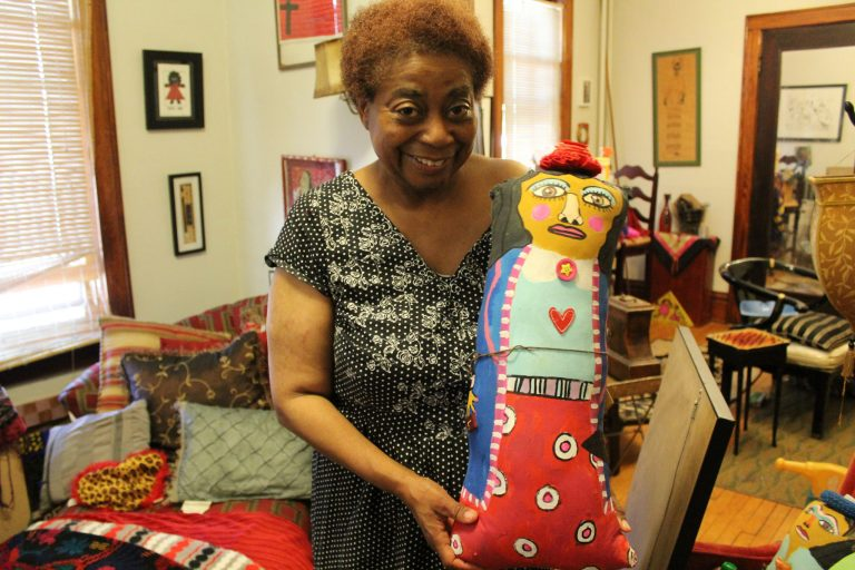 Artist Della Wells displays one of her handmade dolls in her home. Photo by Emmy A. Yates.