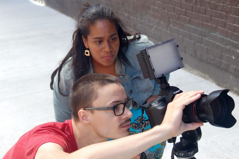 Tyshun Wardlaw directs videographer Mitchell Mittelstedt as he films a muralist working in Black Cat Alley, on the East Side. Photo by Andrea Waxman.