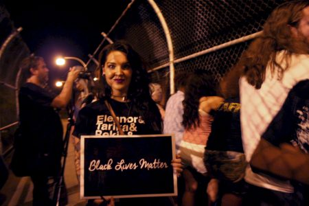"Claire Van Fossen holds a ""Black Lives Matter"" sign during the demonstration. Photo by Jabril Faraj."