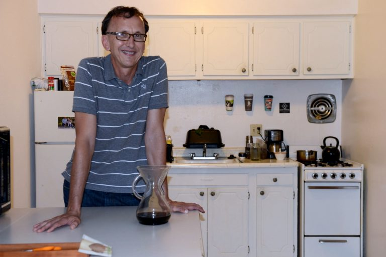 Robert Itzin, who was once chronically homeless, stands in the kitchen of his apartment, provided by Housing First. Photo by Sue Vliet.