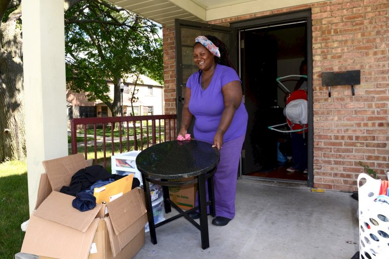 Mateka Young carries a table out of her apartment at 6701 W. Silver Spring Drive. Young was among the first residents to move out of the western section of Westlawn. Photo by Sue Vliet.