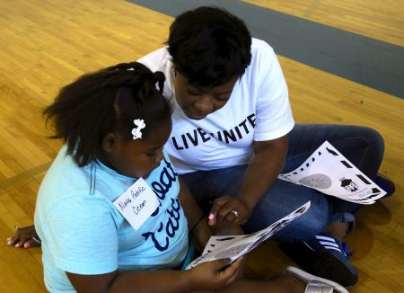 Rockwell intern Marquita Smith, 32, helps a student choose words for a writing activity at the literacy fair. Photo by Amelia Jones.