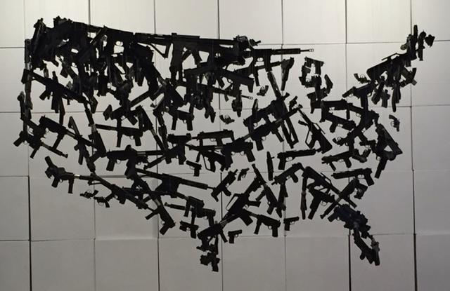 Hanging sculpture of guns. Photo by Craig Mastantuono.