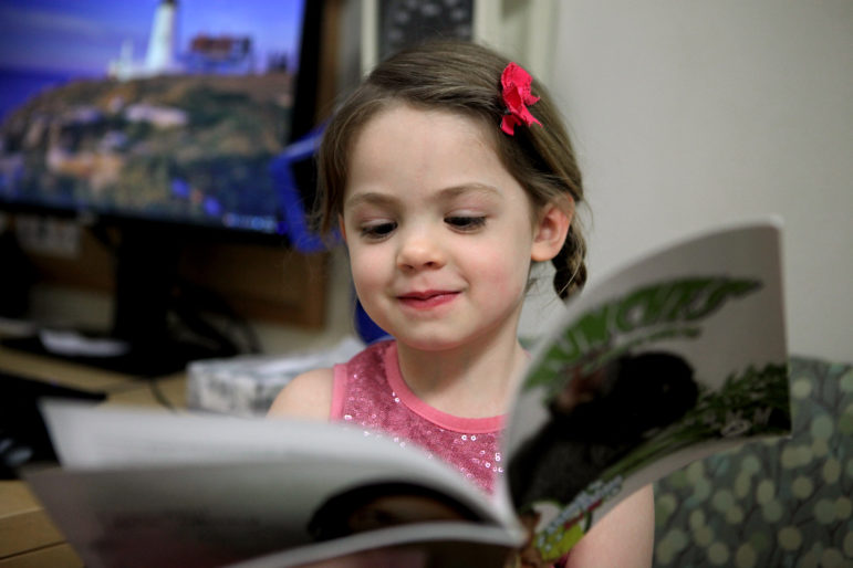 Naja Tunney, 5, reads a book at the Group Health Cooperative health care center in Madison while her sister, Hannah, 2, gets a check-up. GHC participates in the national Reach Out and Read program, which distributes distributes books to children up to age 5 at each regular check-up. The program is designed to encourage families to develop good reading habits. Photo by Coburn Dukehart of the Wisconsin Center for Investigative Journalism.