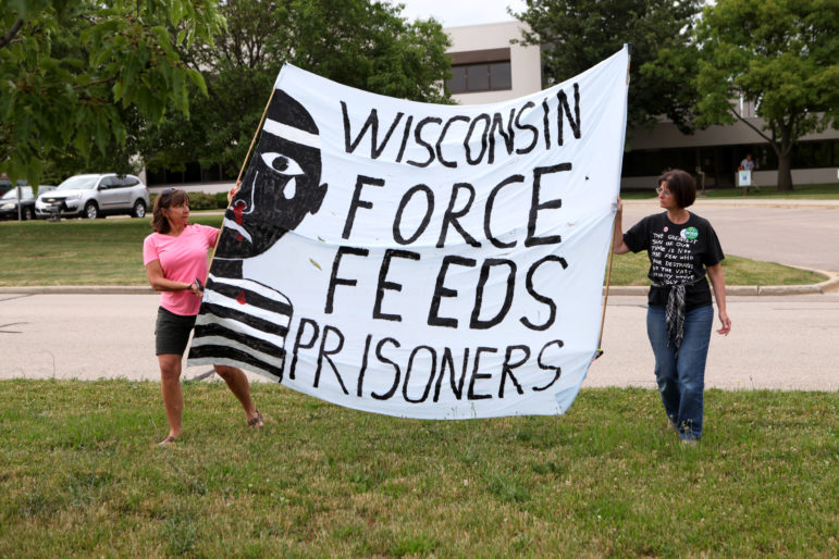 Wendy Turk, left, and Mary Jo Fesenmaier hold a banner decrying the force feeding of Wisconsin prisoners during a rally outside the state Department of Corrections headquarters in Madison on July 5. Hunger striking prisoners and their advocates are seeking an end to long-term solitary confinement. Photo by Coburn Dukehart of the Wisconsin Center for Investigative Journalism.