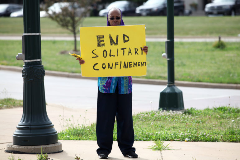 Sister Linda Muhammad holds a sign during a rally outside the state Department of Corrections headquarters in Madison, to protest long-term solitary confinement. Her son, Robert Tatum, was being held in disciplinary solitary confinement at Waupun Correctional Institution. Photo by Coburn Dukehart of the Wisconsin Center for Investigative Journalism.