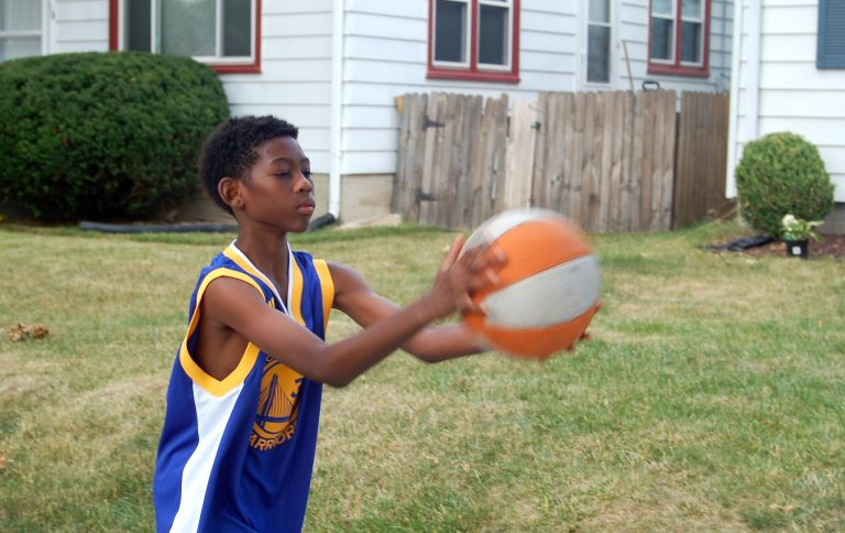 J'Ali Thornton practices with a basketball in front of his house. Photo by Andrea Waxman.